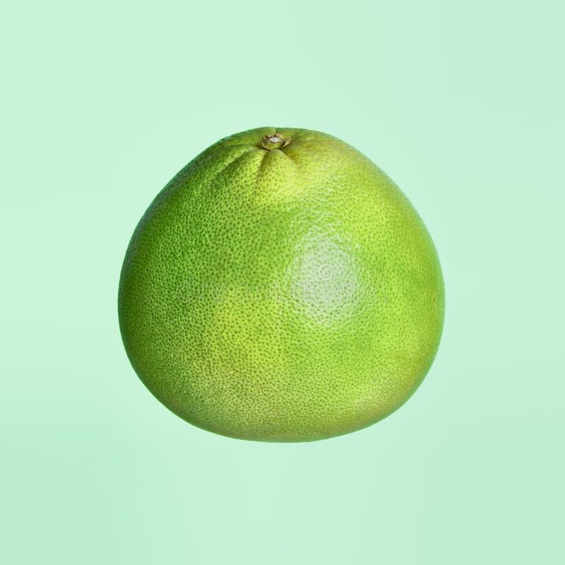 Pomelo verde aislado sobre fondo verde imagen de archivo