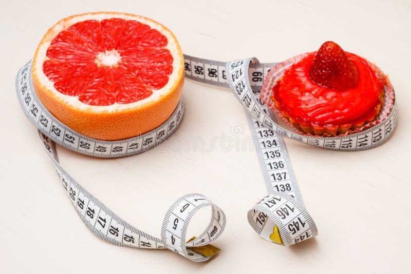Pomelo y torta con la cinta métrica Dieta imagen de archivo libre de regalías