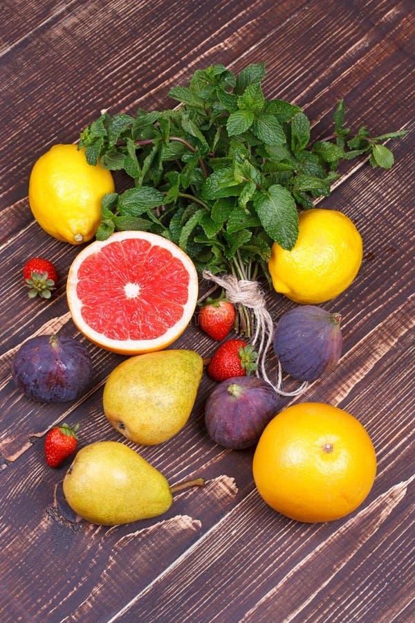 Pomelos, peras, limones, higos, fresa, pomelo, menta en fondo de madera; todavía vida con las frutas imagen de archivo