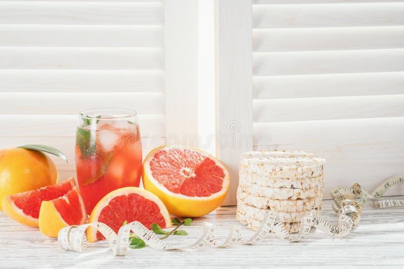 Pomelos y jugo de pomelo fresco, tortas de arroz y cinta métrica, en la tabla de madera blanca rústica enfrente de las persianas, imágenes de archivo libres de regalías