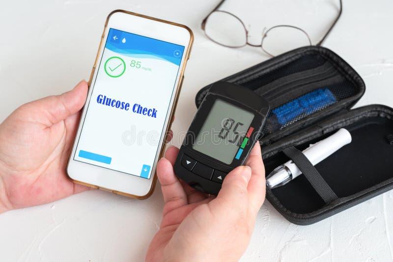 Pomiar poziomu glukozy i używanie smartfona zdjęcia stock