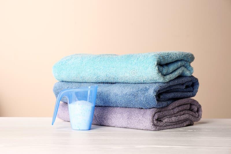 Pomiarowa filiżanka z płuczkowym proszkiem i czystymi ręcznikami obraz royalty free