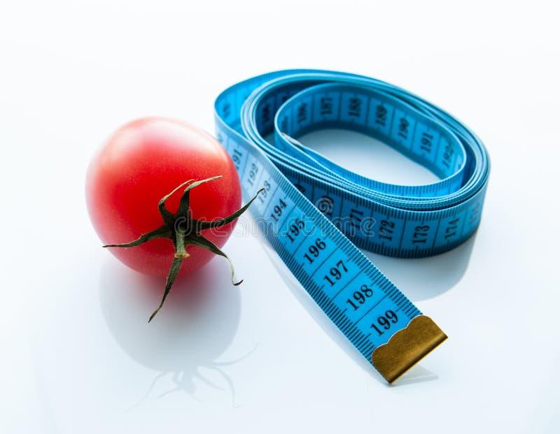 Pomiarowa taśma, soczysty pomidor pojęcie zdrowy odżywianie i ciężar strata, fotografia stock