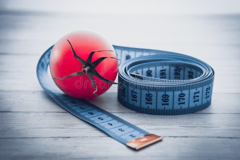 Pomiarowa taśma, soczysty pomidor pojęcie zdrowy odżywianie i ciężar strata, obraz royalty free