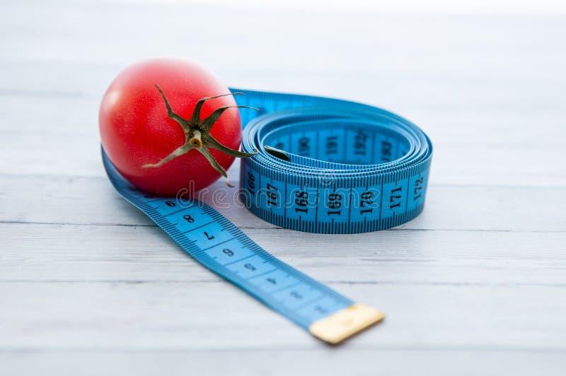 Pomiarowa taśma, soczysty pomidor pojęcie zdrowy odżywianie i ciężar strata, fotografia royalty free
