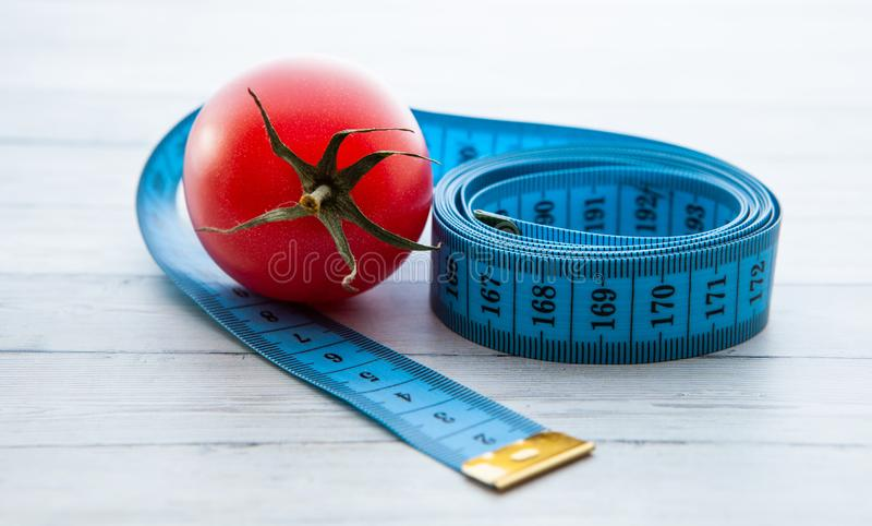 Pomiarowa taśma, soczysty pomidor pojęcie zdrowy odżywianie i ciężar strata, zdjęcie stock