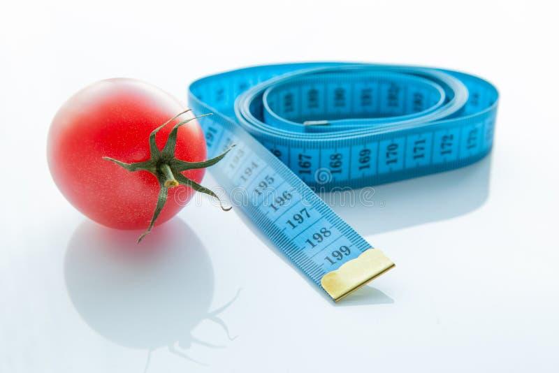 Pomiarowa taśma, soczysty pomidor pojęcie zdrowy odżywianie i ciężar strata, zdjęcia royalty free
