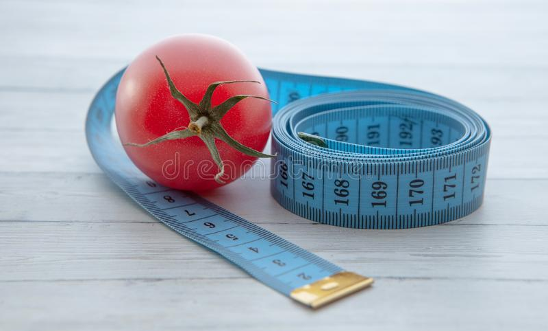 Pomiarowa taśma, soczysty pomidor pojęcie zdrowy odżywianie i ciężar strata, zdjęcie royalty free