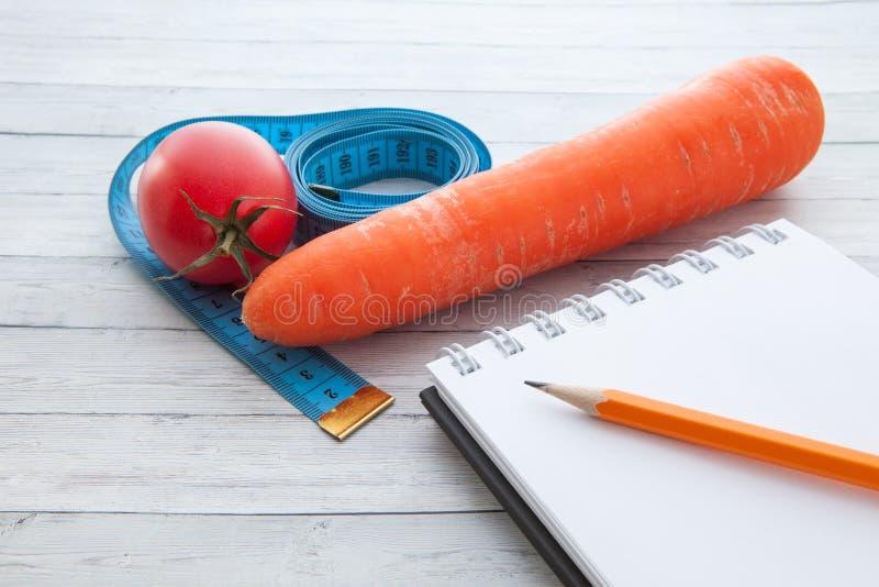 Pomiarowa taśma z notepad, soczystym pomidor, marchewka pojęcie zdrowy łasowanie i ciężar strata, obrazy royalty free