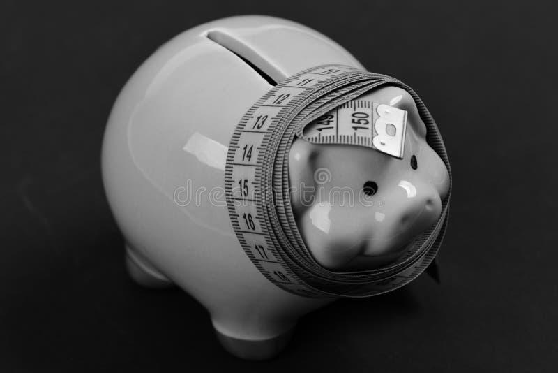 Pomiarowa taśma zawijająca wokoło prosiątko banka lub pieniądze pudełka obrazy stock