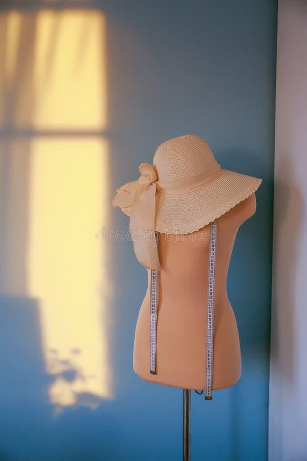 Pomiarowy różowy mannequin z kapeluszową szwaczki mienia taśmą pracuje z atrapą w wygodnym kreatywnie projekta studiu lub krawczy fotografia stock