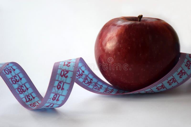 Pomiarowy taśmy i czerwieni jabłko na białym tle obraz royalty free