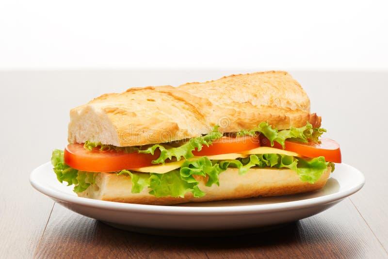 Pomidor, ser i sałatkowa kanapka od świeżego baguette na białym ceramicznym talerzu na jaskrawym jasnobrązowym drewnianym stole, fotografia royalty free