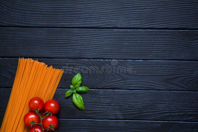 Pomidorowy spaghetti z świeżymi wiśniami i basil leaf na czerni zalecamy się fotografia royalty free