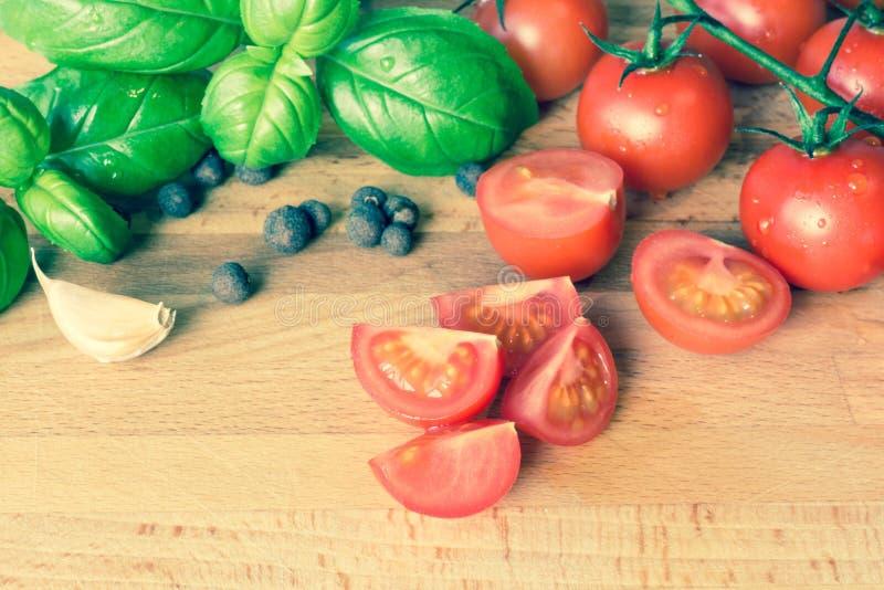 Pomidoru basilu allspice na drewnianym stole i czosnek fotografia royalty free