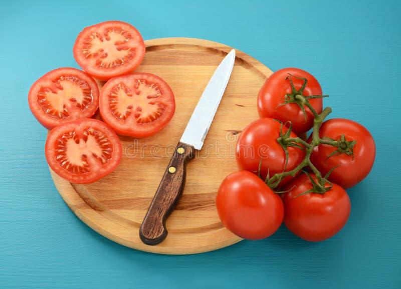 Pomidory, cały i pokrojony z nożem na drewnianej desce obraz stock