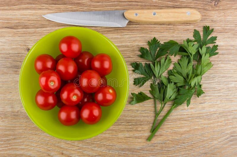 Pomidory czereśniowi w zielonym pucharze, kuchennym nożu i pietruszce, obraz stock