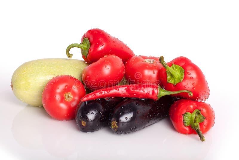 Pomidory, czerwoni słodcy pieprze, gorący chili pieprze, fiołkowe oberżyny, zielony zucchini w kroplach woda fotografia stock