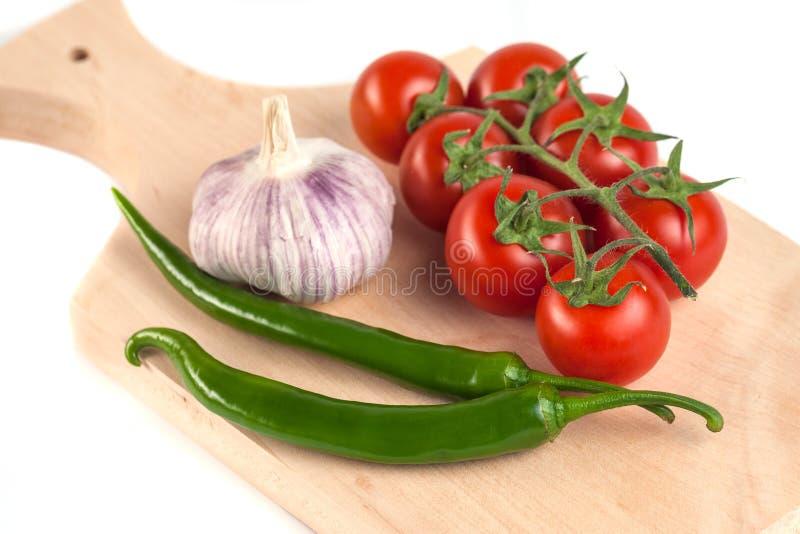 Pomidory, czosnek i zieleni pieprze na drewnianej tnącej desce, zdjęcia stock