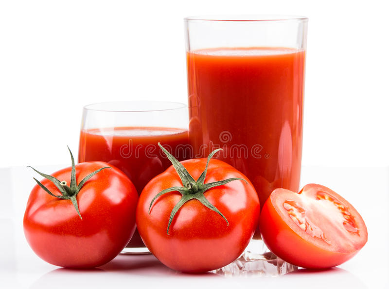 Pomidory i sok w szkle na bielu zdjęcie stock