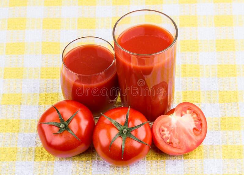Pomidory i sok w szkle na tablecloth fotografia royalty free