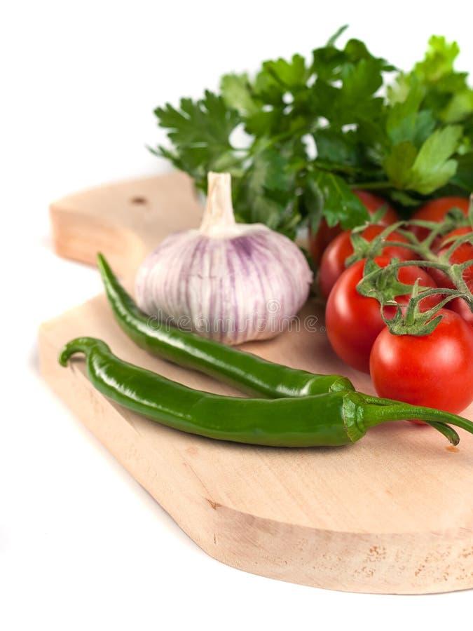 Pomidory, pietruszka, czosnek i zieleni pieprze na drewnianym cuttin, obrazy stock