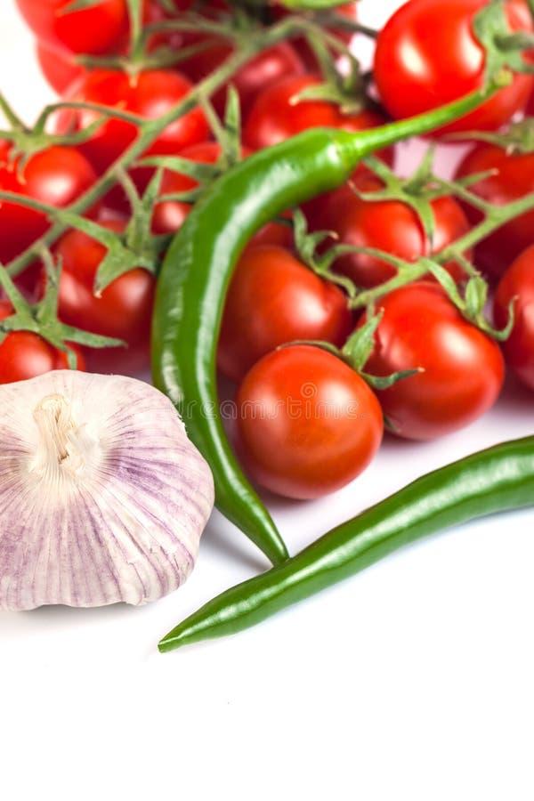 Pomidory, zieleni pieprze i inni warzywa na białym backgrou, obraz royalty free