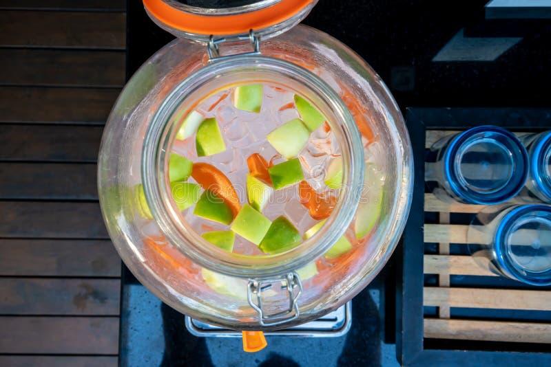 Pomme, carotte et glace vertes dans la bouteille en verre de l'eau infusée par fruit image libre de droits