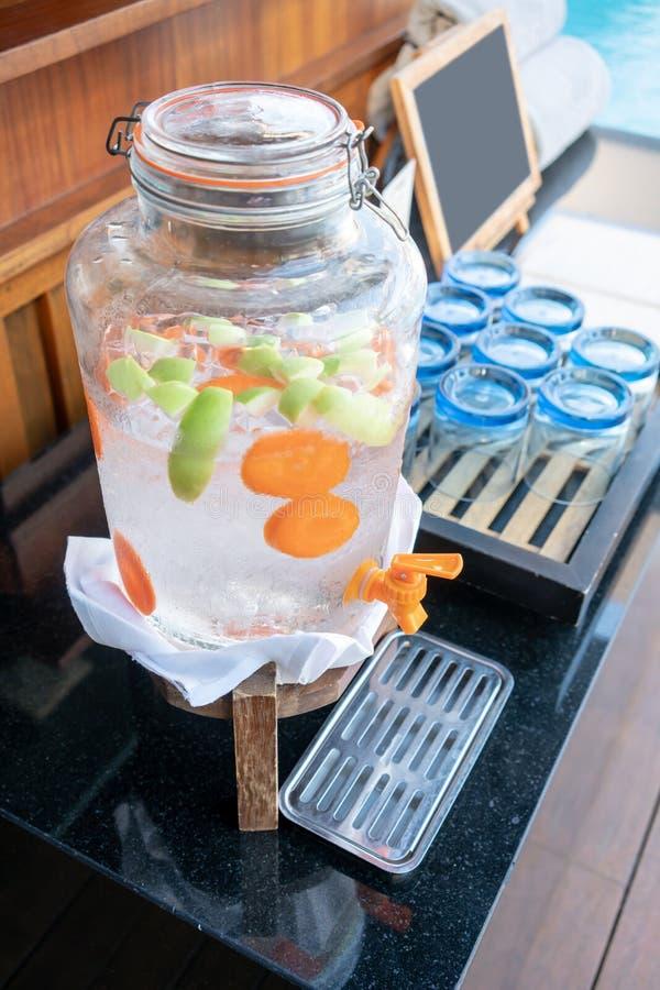 Pomme, carotte et glace vertes dans la bouteille en verre de l'eau infusée par fruit photos stock