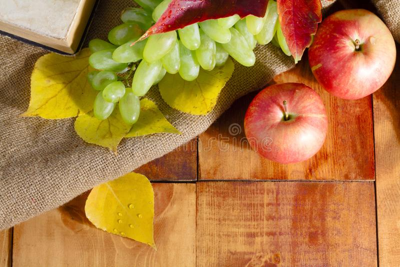 Pomme de récolte d'automne, raisins et feuilles de jaune sur la table en bois photo stock