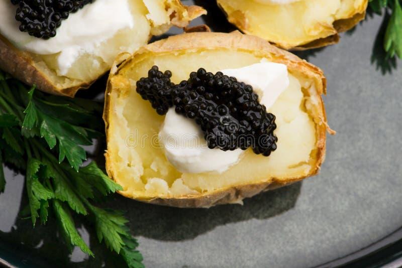 Pomme de terre cuite à la crème épicée, fromage et caviar photo libre de droits