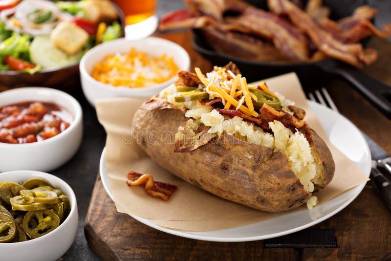Pomme de terre cuite au four chargée avec le lard et le fromage photographie stock libre de droits