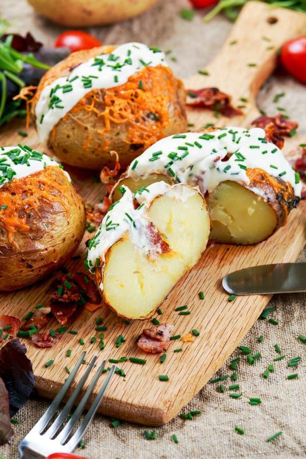 Pomme de terre cuite au four chaude avec du fromage, le lard, la ciboulette et la crème sure image stock