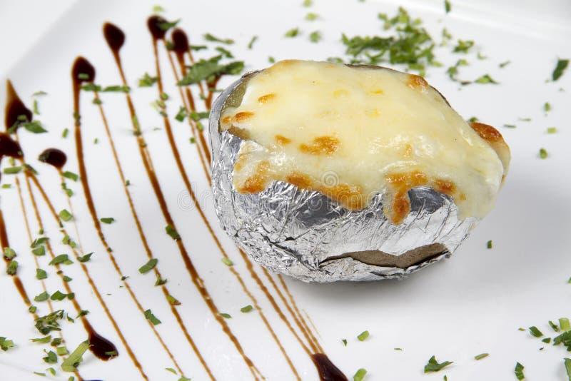 Pomme de terre cuite au four dans l'aluminium avec du fromage image libre de droits