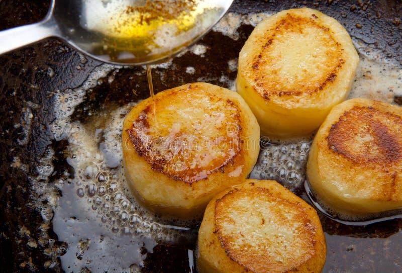 Pomme de terre de fondant faisant frire dans le carter de sauce. beurre arrosant la nourriture avec le spo photographie stock