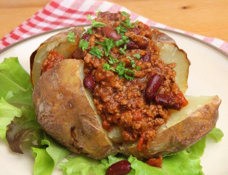 Pomme de terre en robe de chambre avec des piments images stock