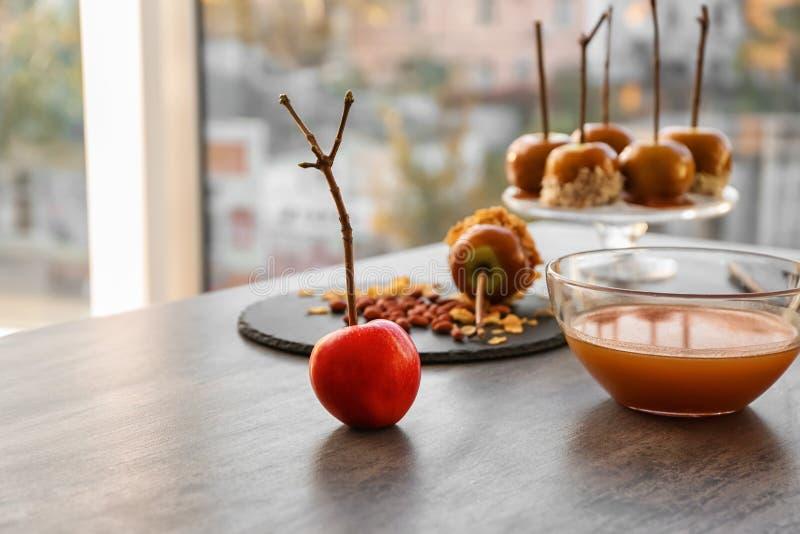 Pomme et bol en verre mûrs avec le caramel sur la table grise photographie stock libre de droits