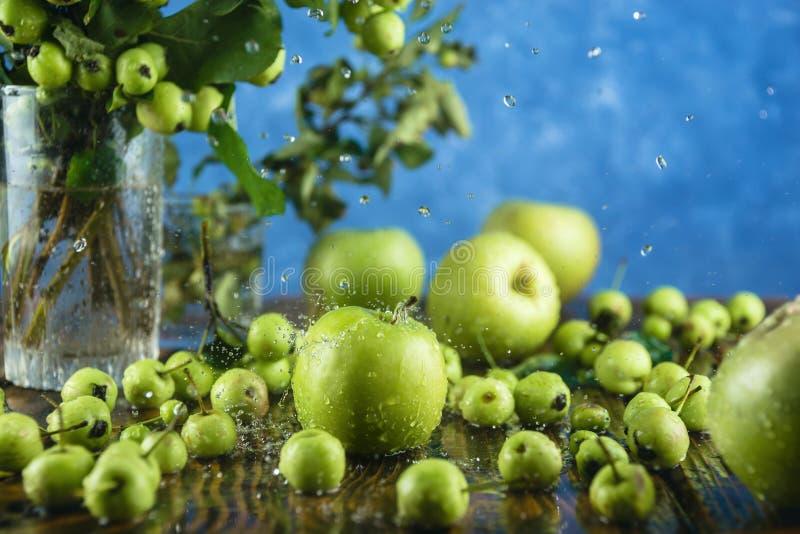 Pomme et branches vertes fraîches sur la table en bois avec de l'eau de éclaboussement en baisse image libre de droits