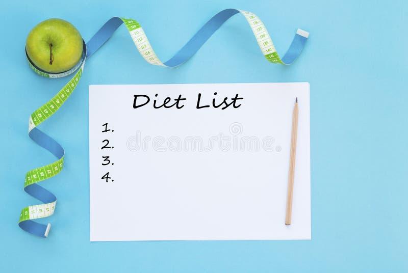 Pomme fraîche, bande de mesure, et liste de régime sur le fond bleu photographie stock