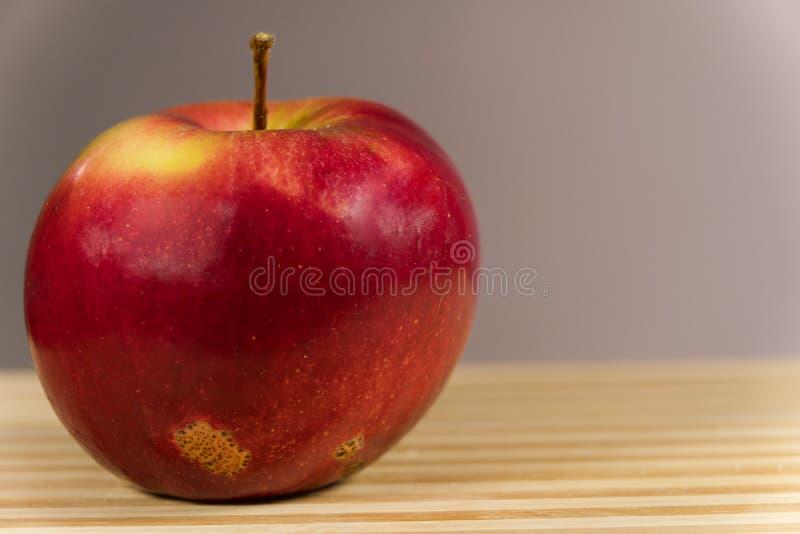 Pomme juteuse isolée sur fond gris sur le bureau images stock