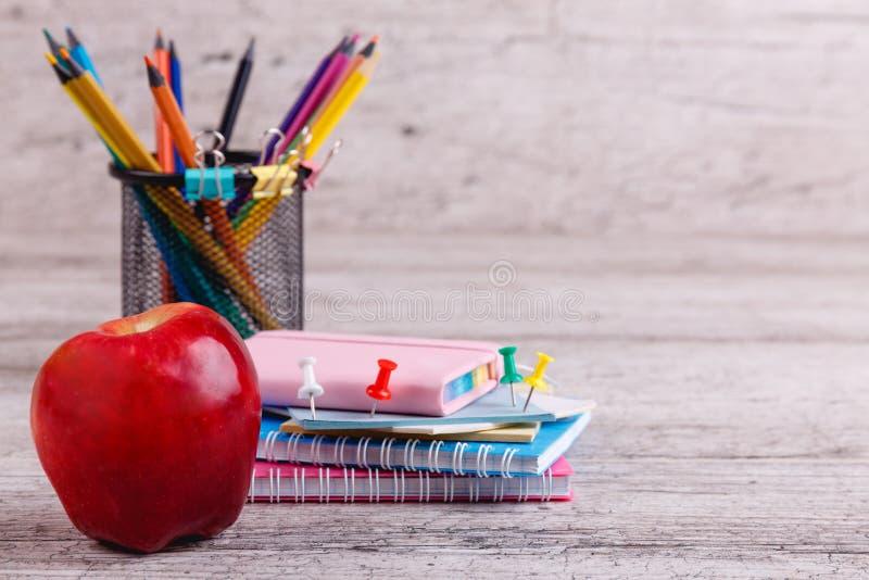 Pomme juteuse rouge, une pile des carnets, crayons colorés dans un récipient Sur une surface en bois image stock