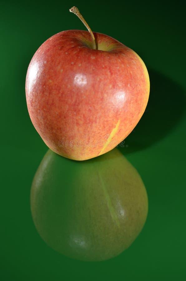Pomme mûre et savoureuse avec la réflexion sur une terre verte photo stock
