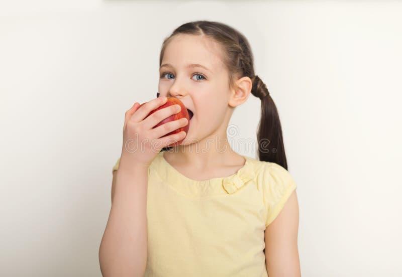 Pomme rouge acérée assez mignonne de petite fille au-dessus du fond blanc photographie stock