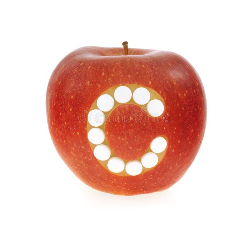 Pomme rouge avec des pillules de vitamine C au-dessus du backgrou blanc images stock