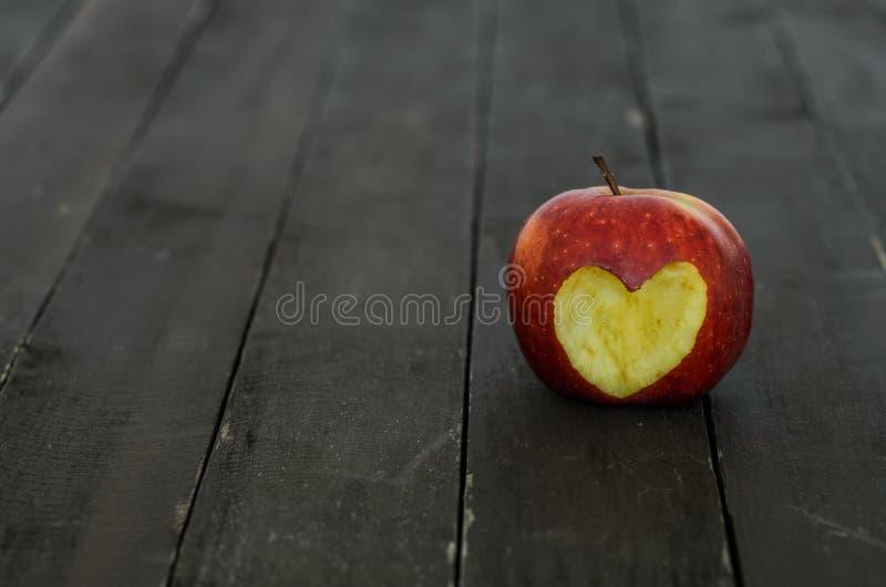 Pomme rouge avec un coeur coupé sur un fond en bois image stock