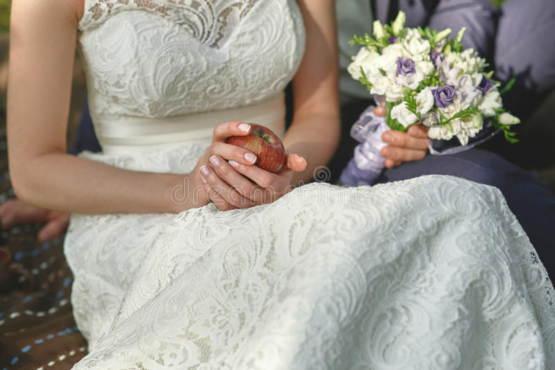 Pomme rouge dans des mains de la jeune mariée dans une robe blanche images stock