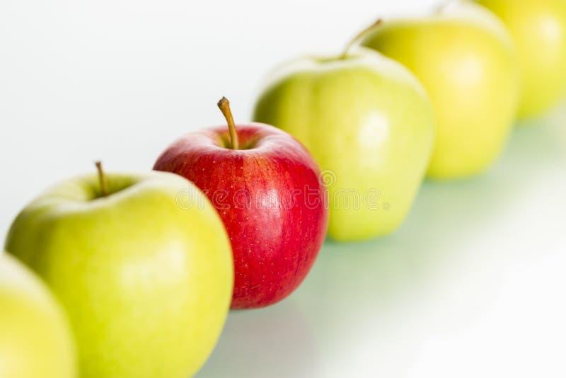 Pomme rouge restant à l'extérieur de la ligne des pommes vertes. photographie stock libre de droits