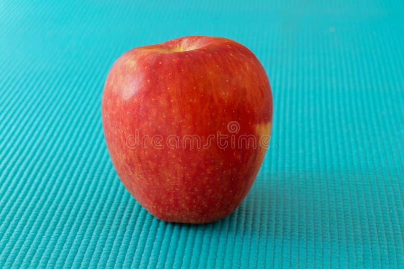 Pomme rouge sur la surface de texture de bleu de ciel photographie stock libre de droits