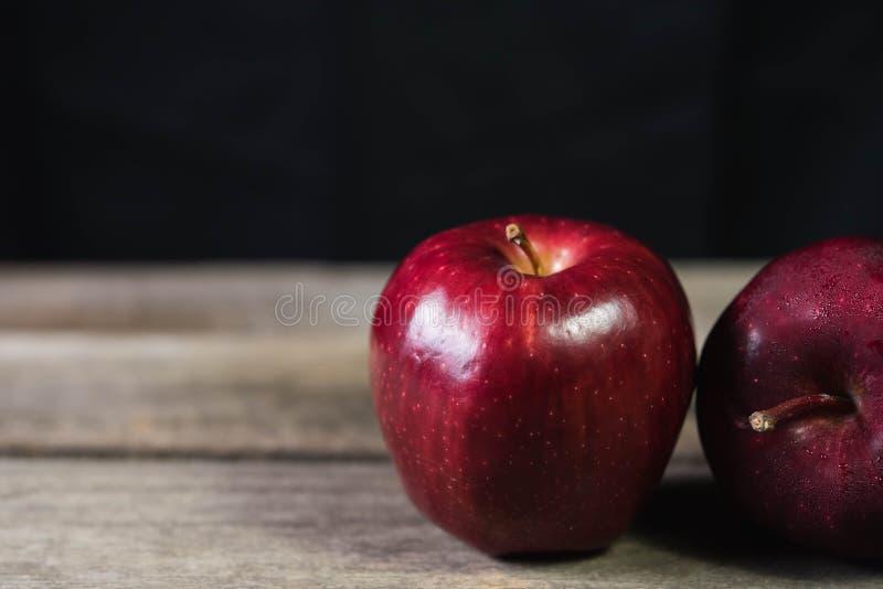 Pomme rouge sur la table en bois sur le fond foncé photographie stock libre de droits