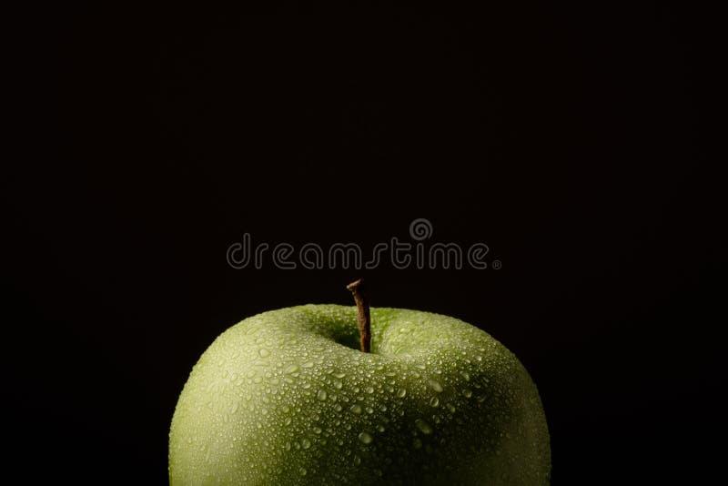 Pomme verte avec des baisses de l'eau sur un fond noir image libre de droits